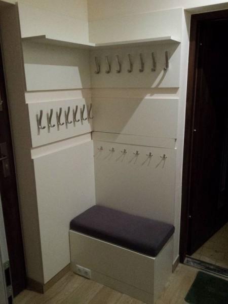 ścianka z wieszakami na ubrania i pufą do siedzenia