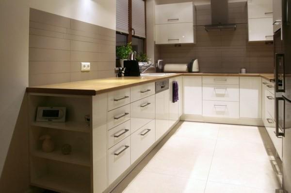 wąska kuchnia z zabudowanymi białymi szafkami