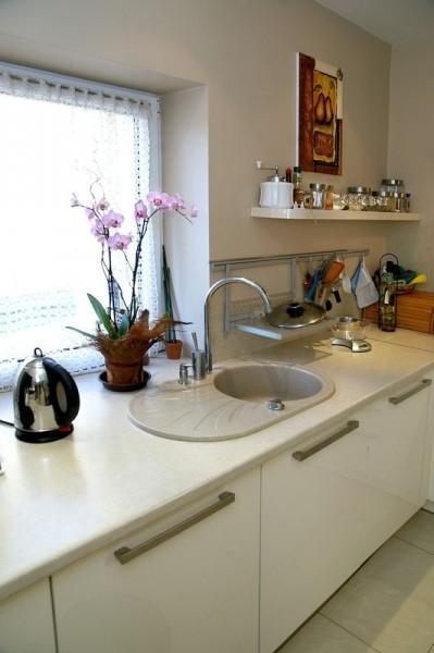 kuchnia z białymi szafkami i zlewem