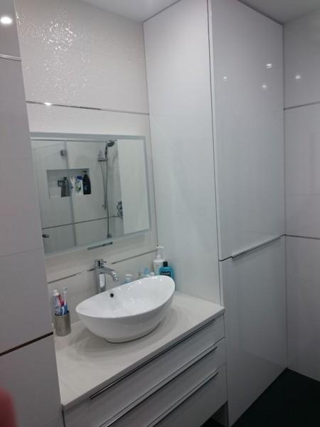 łazienka z dużą białą szafką po prawej
